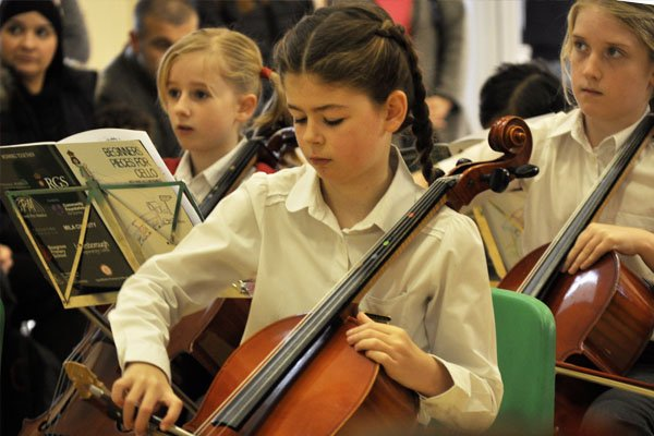 Child at Sandfield school playing the cello on music day